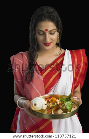 Beautiful woman in a Bengali sari holding pooja thali - stock photo