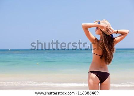 beautiful woman in a bikini on the beach looking on the horizon - stock photo