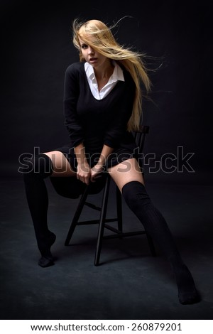 Beautiful woman in a black dress and stockings posing on the chair in studio with dark background . - stock photo
