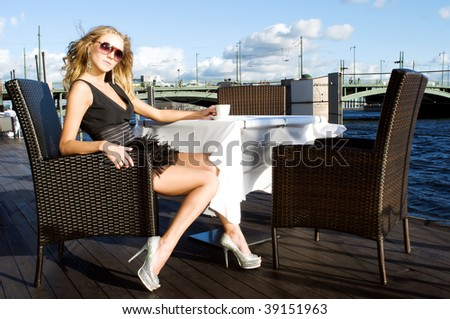 Beautiful woman in a black dress is sitting in the cafe at the river - stock photo