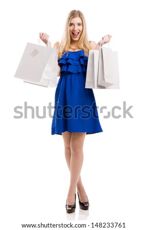 Beautiful woman in a blue dress with a happy face holding shopping bags, isolated on a white background - stock photo