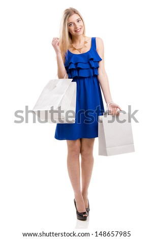 Beautiful woman in a blue dress with shopping bags, isolated on a white background - stock photo
