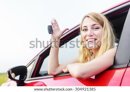 Beautiful woman in a car showing keys. - stock photo