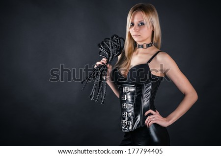 beautiful woman in a corset with a whip in hands - stock photo