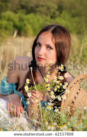 beautiful woman in a field of flowers chamomile with cowboy hat - stock photo