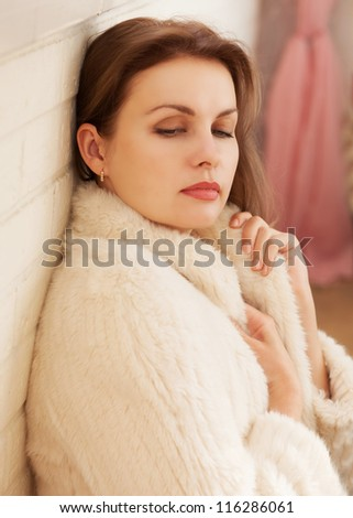 Beautiful woman in a fur jacket sits against the wall - stock photo