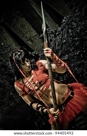 Beautiful woman in a gladiators uniform posing with a spear displaying her strong fit body.