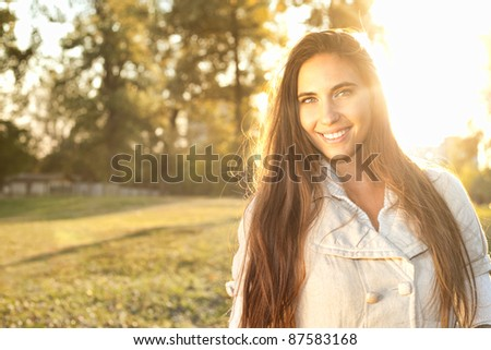 Beautiful woman in a grassy field outdoor backlit by sunlight