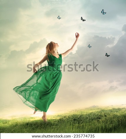 Beautiful woman in a green dress chasing butterflies on a mountain - stock photo