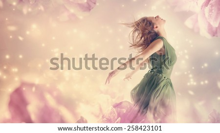 Beautiful woman in a green dress in a pink peony flower fantasy  - stock photo