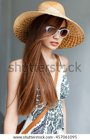 Beautiful woman in a hat and sunglasses on the beach - stock photo