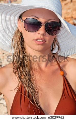 beautiful woman in a hat and sunglasses on the beach in a bikini - stock photo