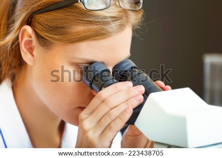 Beautiful woman in a laboratory working with a microscope. - stock photo