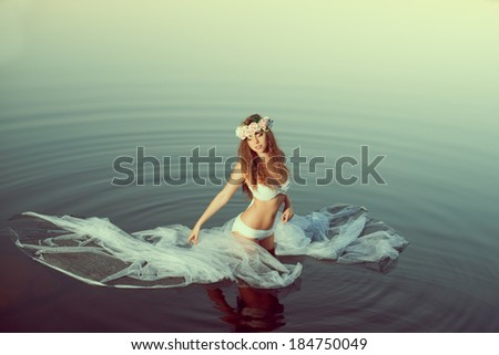 Beautiful woman in a lake at night. Beauty girl at sunset in the lake. - stock photo