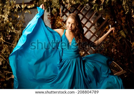 Beautiful woman in a long blue dress. Young girl in luxury fashionable dress