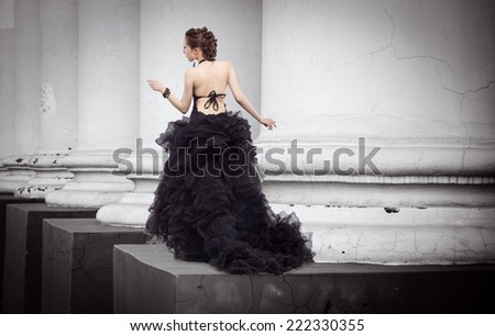 Beautiful woman in a long dress walks along the lush classical architectural columns. - stock photo