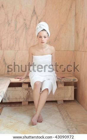 beautiful woman in a marble sauna room - stock photo