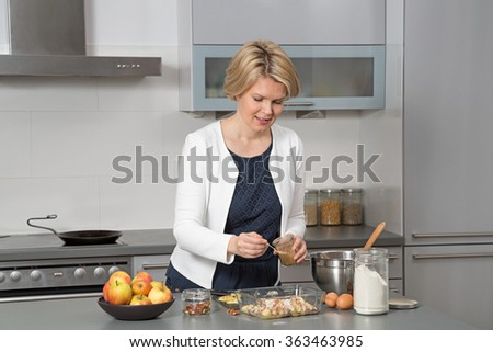 Beautiful woman in a modern kitchen, baking an apple pie