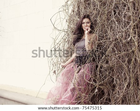 beautiful woman in a pink skirt fashion in the branches of trees - stock photo
