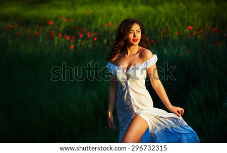 Beautiful woman in a poppy field with flowers. Woman wearing in a white dress. - stock photo