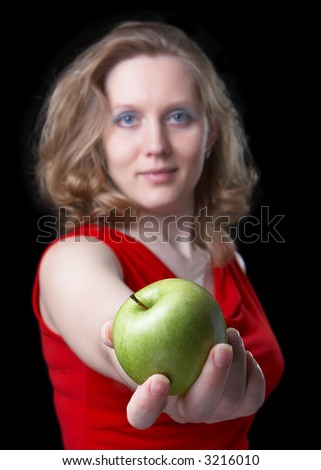 Beautiful woman in a red dress with a green apple in a hand on a black background.  Focus on an apple, and the woman on a background also is dim - stock photo