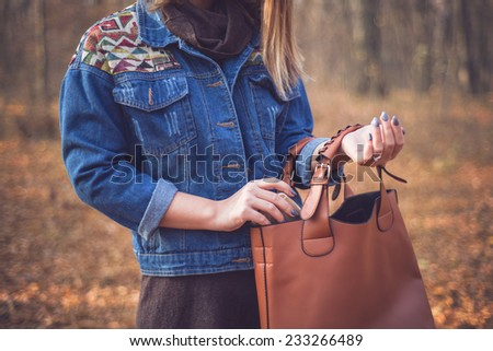Beautiful woman in a romantic autumn fall scenery wearing a denim jacket with geometric print holding a handbag ready for shopping - stock photo