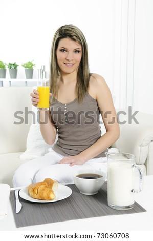 beautiful woman in a sofa is having breakfast - stock photo