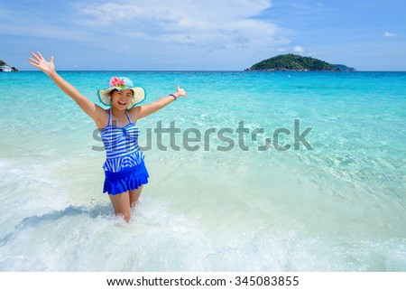 Beautiful woman in a swimwear striped blue hat standing with arms outstretched to life carefree at sea and sky in summer on the beach of Miang Island, Mu Ko Similan National Park, Phang Nga, Thailand - stock photo