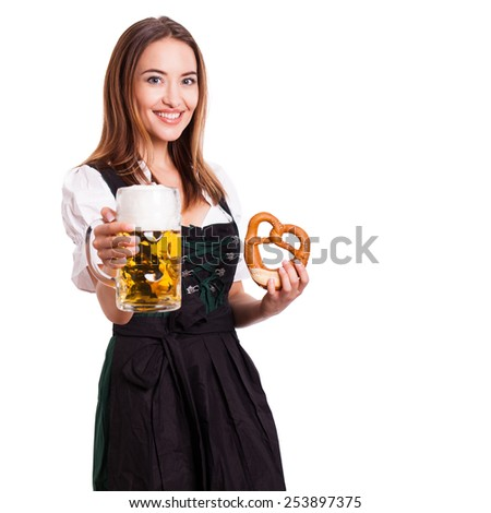 beautiful woman in a traditional bavarian dirndl with beer and pretzel - stock photo