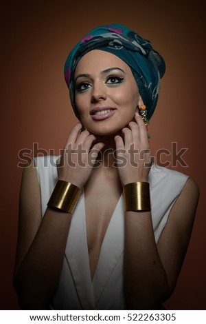 Beautiful woman in a turban.Young beautiful woman with turban and golden accessories.Beauty fashionable woman with hairs wrapped in turban. Pretty Caucasian model wearing earrings posing in studio.