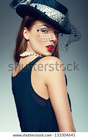 Beautiful woman in a vintage hat over a grey background