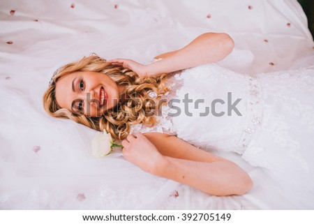 Beautiful woman in a wedding dress. She is in the bedroom with luxurious interior