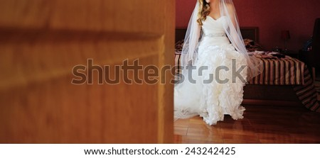 Beautiful woman in a wedding dress sitting on  bed in hotel room, whaiting for groom.  - stock photo