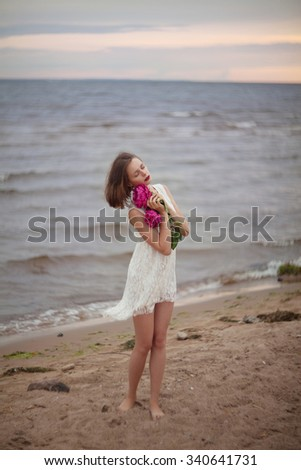 Beautiful woman  in a white dress with peonies in her hands on the sunset beach