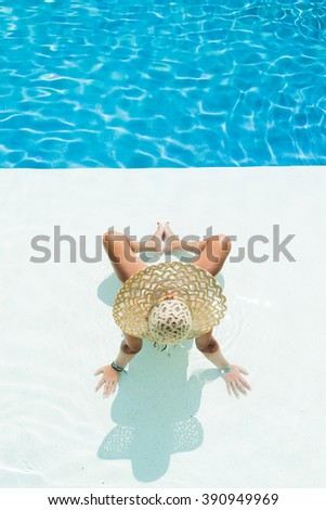 beautiful woman in a white hat sitting at the swimming  pool