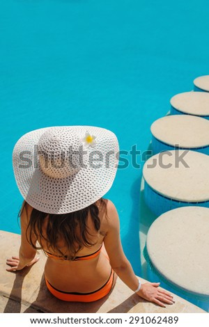 beautiful woman in a white hat sitting on the edge of the pool - stock photo