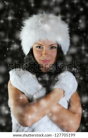 Beautiful woman in a winter hat in the snow on a black background - stock photo