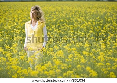Beautiful woman in a yellow flowers field - stock photo