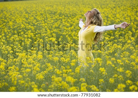 Beautiful woman in a yellow flowers field with arms outstretched - stock photo