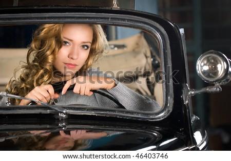 beautiful woman in an old car - stock photo