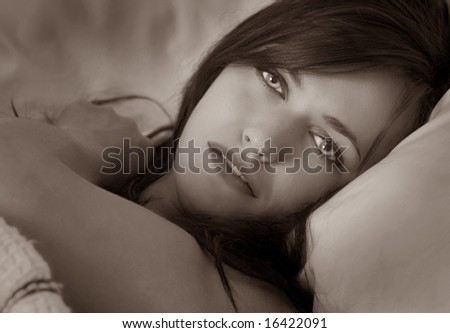 Beautiful Woman in bed with desire in her eyes - stock photo