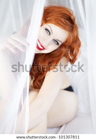 Beautiful woman in bed with mosquito net