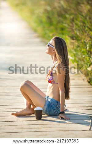Beautiful woman in bikini happy smiling sitting on bridge and looking to the sun. daylight
