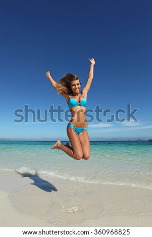 Beautiful woman in bikini jumping on tropical beach - stock photo