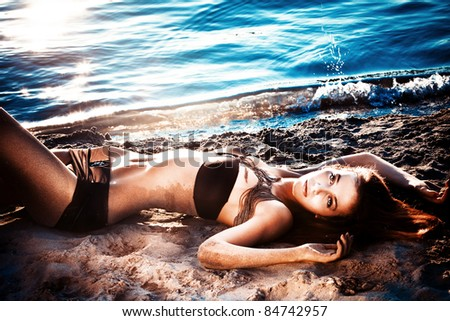 beautiful woman in bikini lying in sand by river, sunset - stock photo