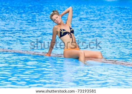 Beautiful woman in bikini near swimming pool