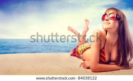 Beautiful woman in bikini sunbathing at the seaside - stock photo