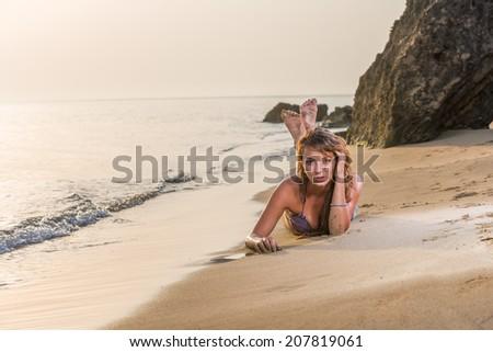 Beautiful woman in bikini top and jeans on the beach. Bali. - stock photo