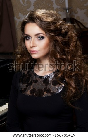 Beautiful woman in black classical dress pose in studio. Vogue style photo.                - stock photo