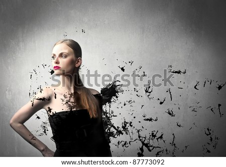 Beautiful woman in black dress exploding into black pieces